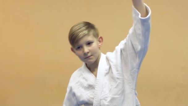 Kleiner Junge beim Kampfsport-Training in der Turnhalle.