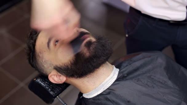 Pohledný vousatý muž v holičství.