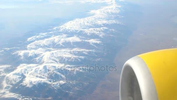 Pohled na zasněžené hory z letadla
