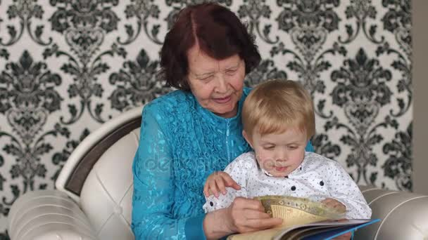 Old grandmother with a grandson sitting on couch.