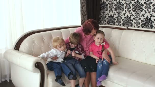 Loving grandma kisses her small grandchildren.