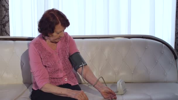 Old woman measures her blood pressure at home.