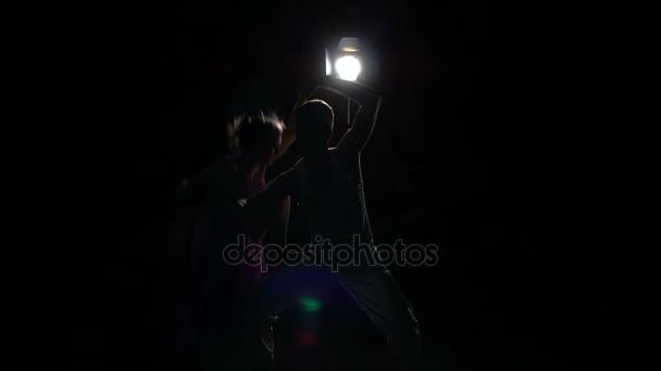 Pair dancers dancing modern choreography in dark.