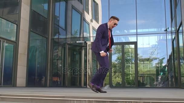 Podnikatel happy dancing poblíž kancelářská budova