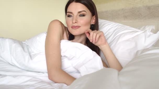 Usmívající se žena probuzení po spánku na posteli. 4k
