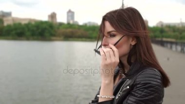 Portrait of girl in sunglasses on bridge of river.