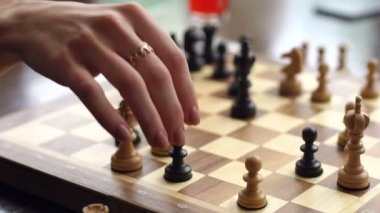 Close-up of females hand with ring playing chess.