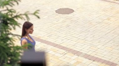 Girl walks down the street and looking at camera.