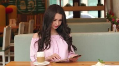Young happy woman using tablet computer in a cafe.
