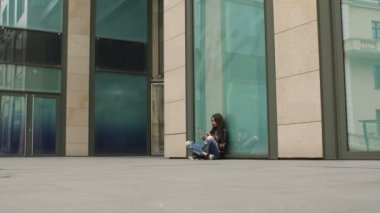 Girl sitting on ground with tablet leaning on wall