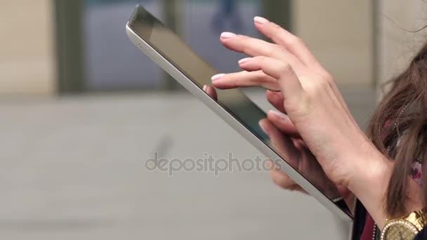 Üzletasszony tartja a kezében tabletta, közelkép.