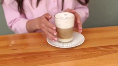 Girl holding a Cup of coffee, close-up of hands.