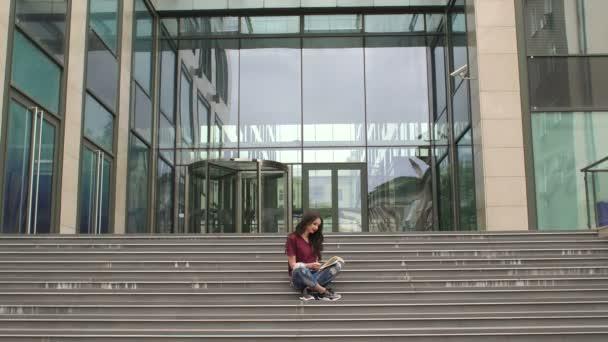 Dívka s knihou sedí na schodech venku. 4k