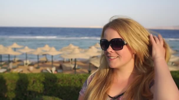 Portrait of a girl in sunglasses on the beach.