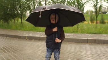 Little boy plays with an umbrella in a rainy day.