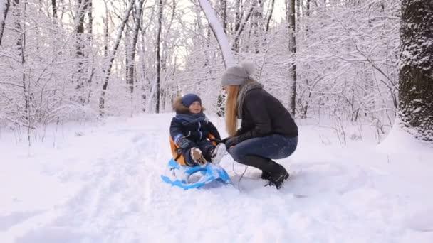 Mutter mit Sohn spaziert mit Schlitten durch verschneite Gasse