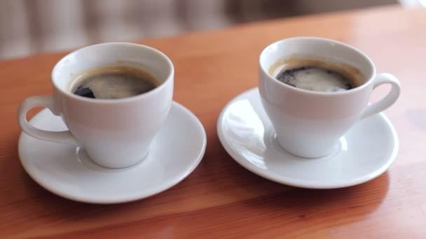 Detail ze dvou šálků kávy na stole