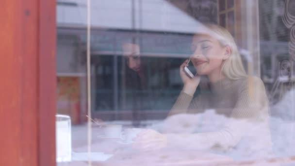 Dvě dívky sedí v kavárně s telefony v zimě