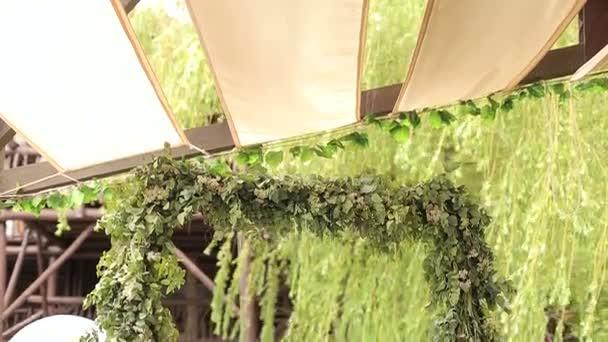 Svatební oblouk zelených větví venku v kavárně.