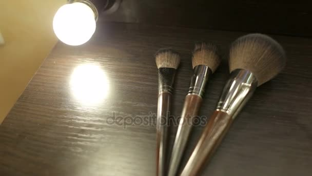 Close-up of three make-up brushes on the table.