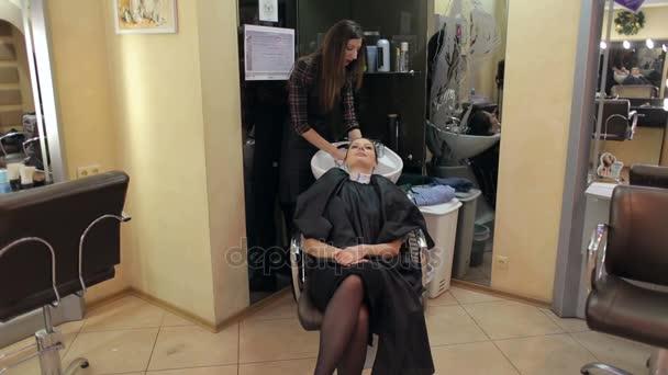 Barber myje vlasy dívky v holičství