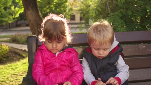 Portrait Of Two Sad Children On A Park Bench Stock