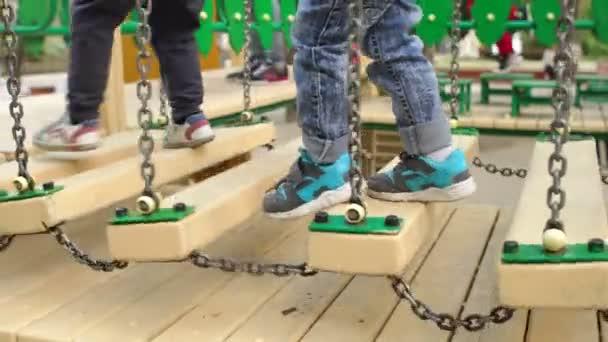 Die Beine des Kindes auf einer Holzbrücke. Spielplatz.