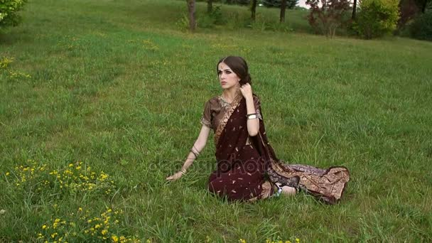 Porträt eines indischen Mädchens im Sari im Gras.