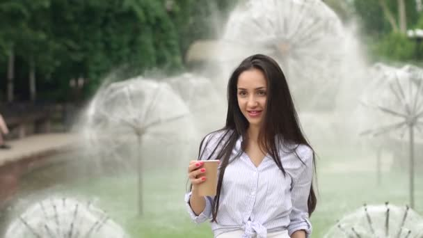 Girl with Cup of coffee on background of fountain.