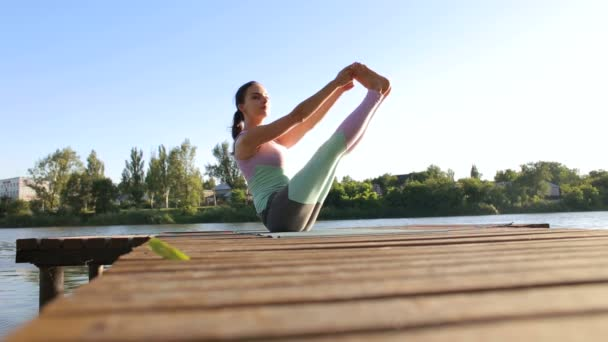 Girl doing yoga on wooden pier by lake in morning.