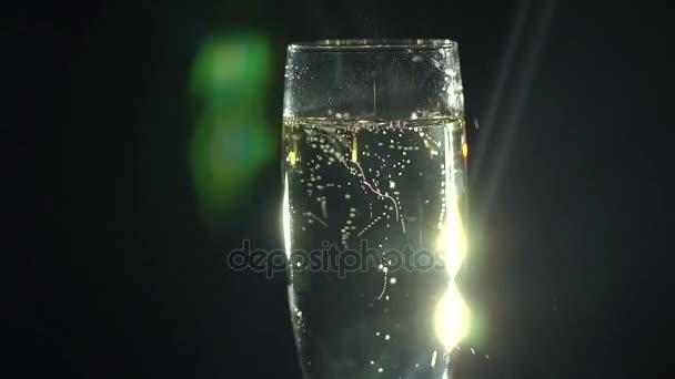 Detailní záběr na sklenku šampaňského na černém pozadí.