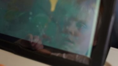 Face of little boy reflected in screen of tablet.