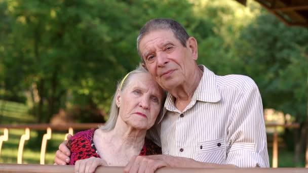 Starý sad babička a děda jsou objímání v parku.