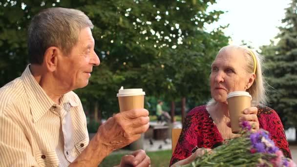 Starší pár pití čaje v pouliční kavárně.