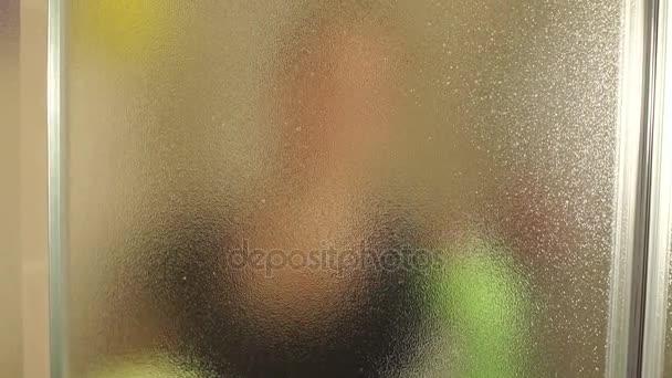 Porträt einer jungen Frau, die Duschtür putzt.