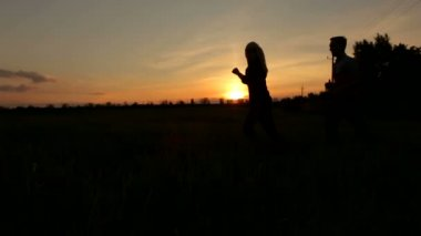 Silhouette of couple having fun on field at sunset