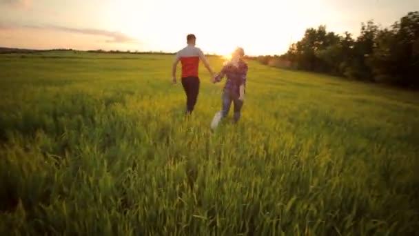Mladý šťastný pár vede přes pole při západu slunce