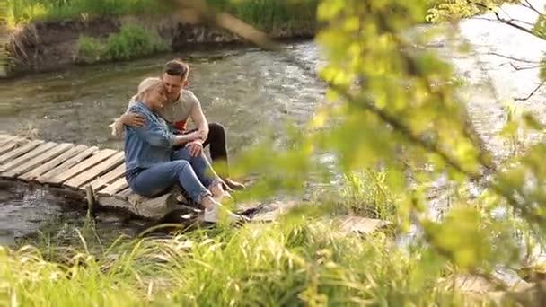 Szerelmesek férfi és a nő ül a fa footbridge.
