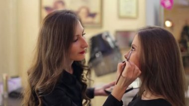 Makeup artist making professional makeup for woman