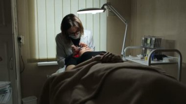 Professional lash maker working with customer.