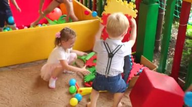 Little children play with puzzles on Playground.