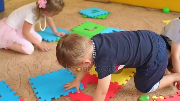 Children gather large soft puzzle sitting on floor