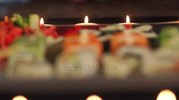 Nahaufnahme von Sushi mit Kerzen im Hintergrund