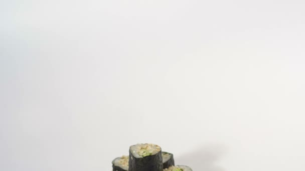Maki roll with cucumber and sesame seeds on white.
