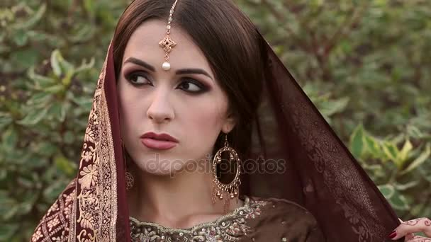 Porträt einer indischen Braut mit verdecktem Kopf im Park