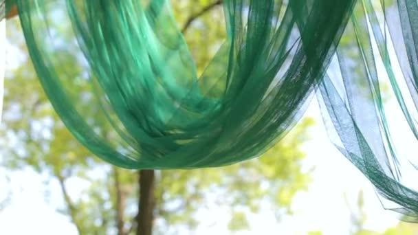 Svatební dřevěná oblouk s zelené a bílé tkaniny.
