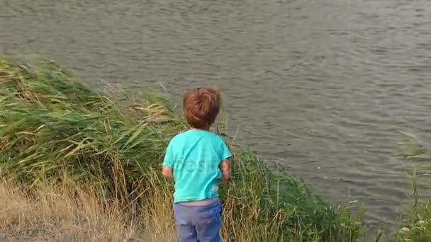 Malý chlapec házet kameny do jezera, pomalé mo