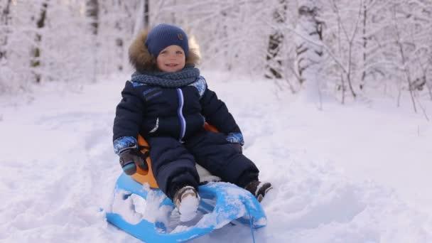 glücklicher lachender Junge, der im Winter auf einem Schlitten sitzt