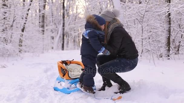 Mutter hilft, einen kleinen Jungen im Schlitten zu setzen.