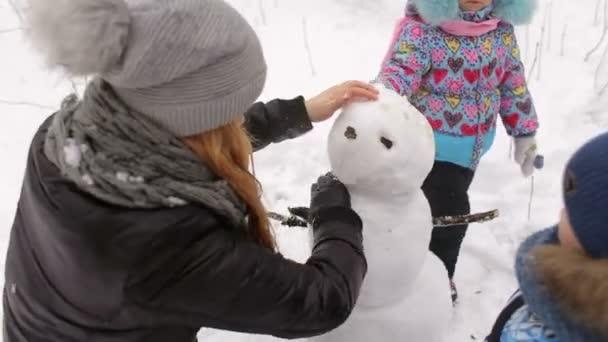 Šťastné matky s dětmi sněhuláka v parku.